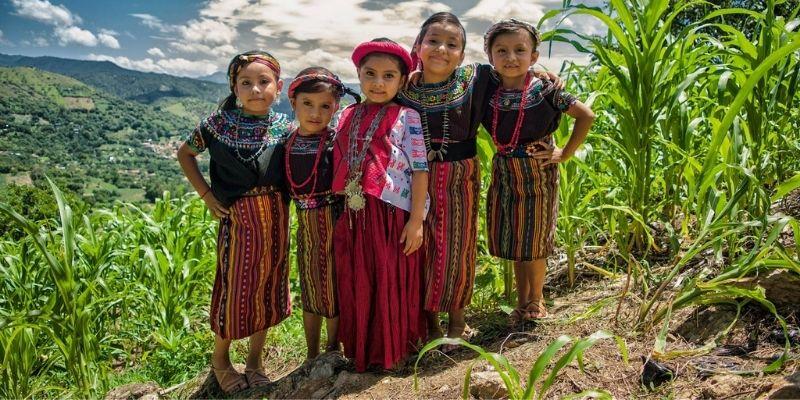 Descripción de foto - niñas de Cubulco, Baja Verapaz, abrazadas el cielo, la naturaleza y la montaña de fondo. - Municipalidad de Cubulco