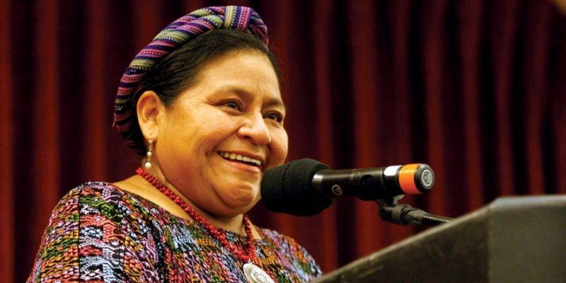 Descripción de la foto - Rigoberta Menchú Tum parada frente al podio, sonriendo mientras hablar por el micrófono - Crédito Revista con la A