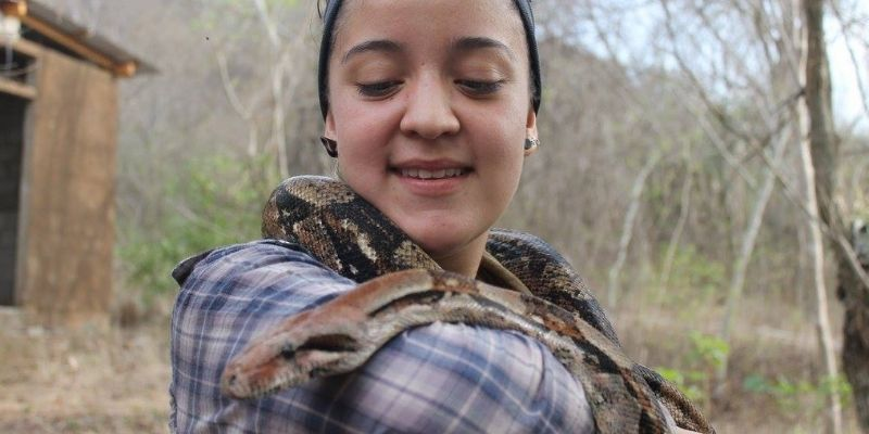 Descripción de foto - mujer sosteniendo una serpiente en su cuello y brazo. - Crédito de foto - Marcela Zaghi