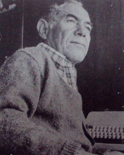 Biografía de Miguel Ángel Vásquez - Descripción de foto - Miguel Ángel Vásquez viendo al horizonte, foto a blanco y negro, detrás de él está su máquina de escribir - Crédito Diario el Gallo