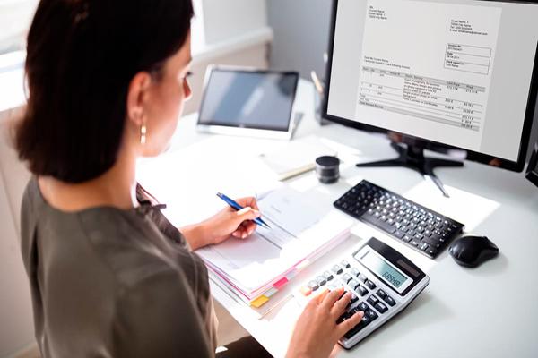 Cómo tramitar documentos tributarios en línea, Guatemala - Descripción de foto - mujer haciendo cuentas en una calculadora, mientras anota y observa la computadora con una factura