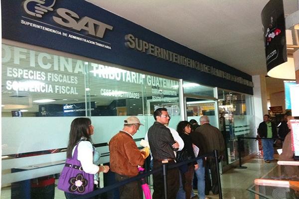 Dar de baja a un contribuyente fallecido en Guatemala - Descripción de la foto - personas haciendo fila afuera de una oficina tributaria - Crédito Asisehace
