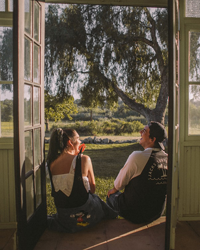 Descripción de foto - Un hombre y una mujer riéndose en la entrada de su casa con un paisaje natural. - Crédito de foto - @jmvillejo