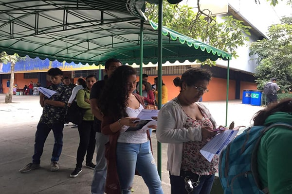 Descripción de la foto - Estudiantes de la USAC haciendo cola, mientras esperan y leen el boletín - Crédito Universidad de San Carlos de Guatemala 2.0