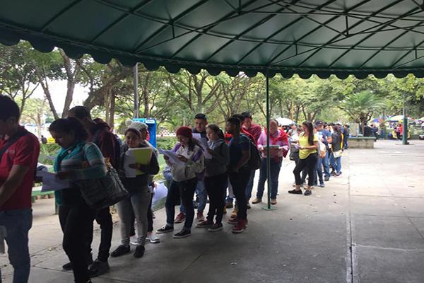 Descripción de la foto - Estudiantes de la USAC haciendo cola y leyendo el boletín del día - Crédito Universidad de San Carlos de Guatemala 2.0