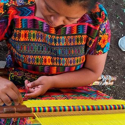 Descripción de la foto - Mujer realizando un tejido típico de colres llamativos como el amarillo, el rojo, el verde y el rosa - crédito de la foto - @guate4you - Instagram