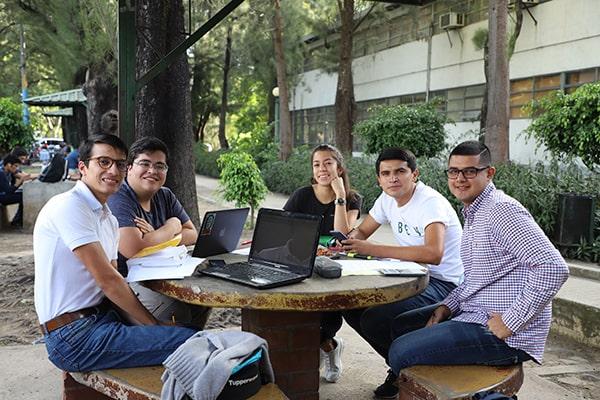 Descripción de la foto estudiantes de la USAC sentados en las afueras de las instalaciones estudiando - Crédito Soy Usac