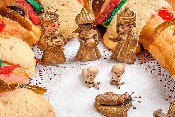 Descripción de la foto - los tres reyes magos en miniatura, en medio de la rosca de reyes, contemplando al niño Jesús en miniatura - Foto Sección Amarilla
