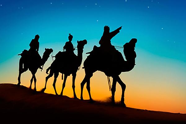 Descripción de la foto, los tres reyes magos sobre sus camellos apuntando con un dedo al cielo - Crédito LatinOL