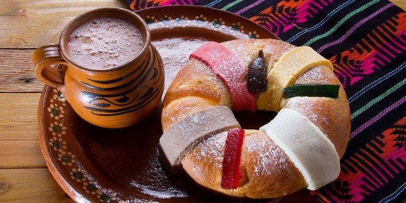 Descripción de la foto - rosca de reyes sobre un plato de barro junto a una taza de cacao caliente - Foto cocina fácil