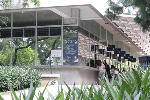 Descripción de la foto: vista del edificio de inscripciones con estudiantes de la USAC realizando pagos. (Crédito: El Sancarlista U)
