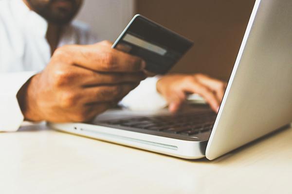 Descripción de la foto: hombre frente a la computadora, ingresando el número de su tarjeta. (Crédito @rupixen)