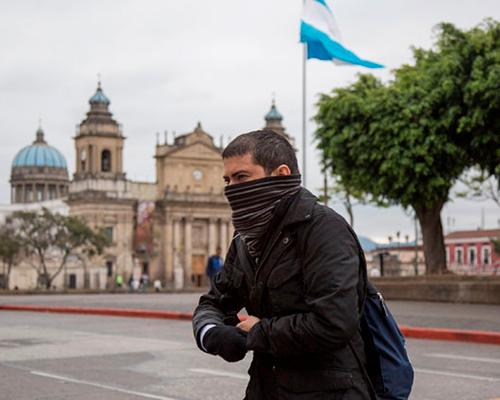 Descricpión de foto - Hombre caminando por la plaza central, curbiendo sus manos con guantes. . - Crédito de foto - Nuevo Diario Ni