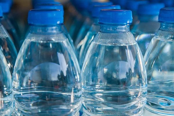 Descripción de foto - Acercamiento a botellas de agua potable de plástico de color azul. - Crédito de foto - TICbeat