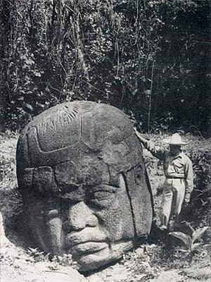 Descripción de foto - Arqueólogo a la par de una cabeza colosal Olmeca tallada en piedra, a blanco y negro. - Crédito de foto - Laura S