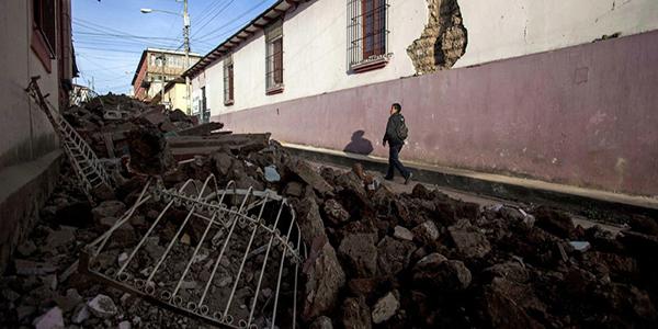 Descripción de foto - Calles del centro histórico con escombros debido a tembrol, mientras un hombre camina al lado. - Crédito de foto - UN News
