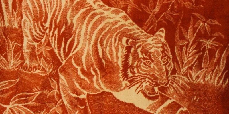 Descripción de foto - Cobertor de empresa San Marcos con una estampa detigre amarillo con fondo rojo. - Crédito de foto - Alto Nivel