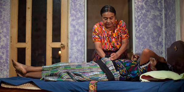 Descripción de foto - Comadrona palpando el estómago de una mujer embarazada. - Crédito de foto - El país