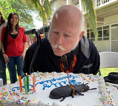 Descripción de foto - Doctor Schuster en el campus de la UVG, soplando unas velas sobre su pastel de cumpleaños - Crédito de foto - Vanesa Granados Barnéond