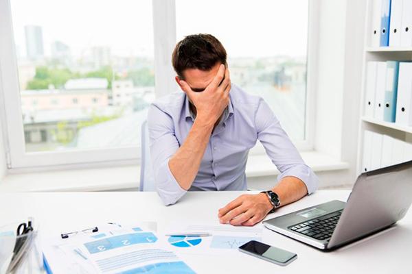 Descripción de foto - Hombre dentro de una oficina sosteniendo su rostro expresando cansancio. - Crédito de foto - TICbeat