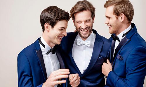 Descripción de foto - Hombres, de diferentes edades, vestidos de traje riendo juntos. - Crédito de foto - Saúl E. Méndez
