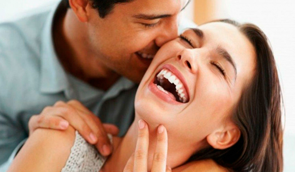 Descripción de foto - Hombres hablándole al oído a una mujer, mientras ella ríe. - Crédito de foto - Seguimiento . com