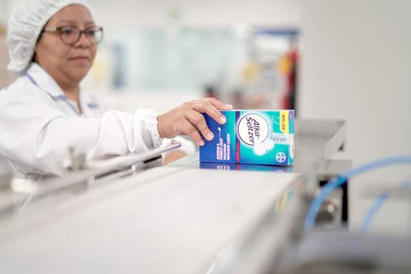 Descripción de foto - Mujer en el laboratorio sosteniendo una caja de Alka Seltzer. - Crédito de foto - Estrategia & Negocios