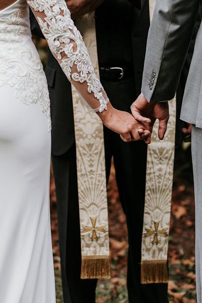 Descripción de foto - Mujer vestida y hombre vestido de novio tomados de la mano frento a un ministro religioso. - Crédito de foto - @zelleduda