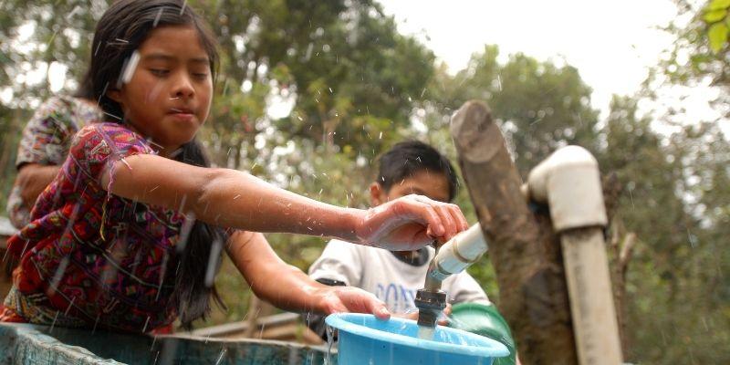 Descripción de foto - Niña vestida de huipil, con palangana echando agua potable en el huacal.- Crédito de foto - Alianza por la solidaridad