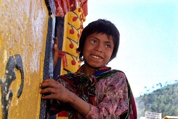 Descripción de foto - Niño vistiendo colorido traje típico en frente de la Iglesia de San Andrés Xecul Guatemala. - Crédito de foto - RFoxPhotography