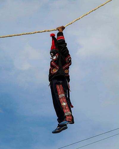 Descripción de foto - Personas vestidas con el traje ceremonial de los micos colgado de una cuerda. - Crédito de foto - Diseños Yhensel