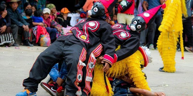 Descripción de foto - Personas vestidas con el traje ceremonial de los micos unos encima de otros. - Crédito de foto - Diseños Yhensel