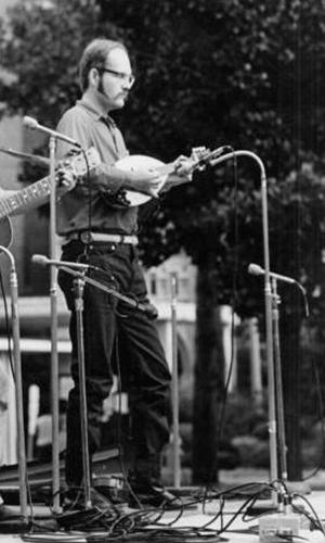 Descripción de foto - Schuster de joven, tocando la mandolinda en un escenario en Estados Unidos. - Crédito de foto - Discogs