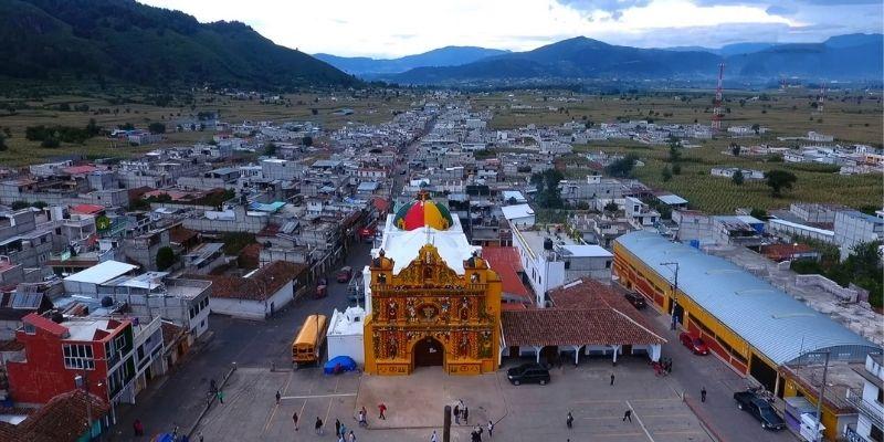 Descripción de foto - Vista de la plaza central de San Andrés Xecul con vista a las montañas. - Descripción de foto - Tujaal Radio