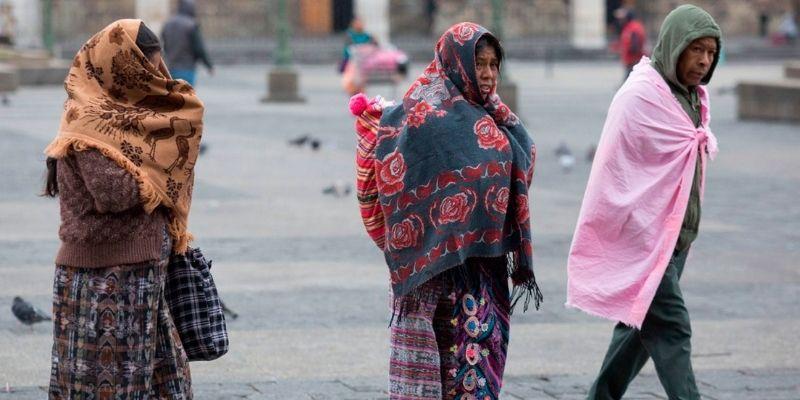 Descripción de foto - dos mujeres y un hombre abrigados con chamarras y telas mientras caminan por el parque central. - Crédito de foto - DCA