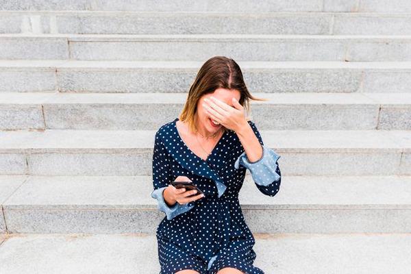 Descripción de foto - mujer sentada sobre unas gradas, ocultando su rostro con una media sonrisa. - Crédito de foto - Pinterest