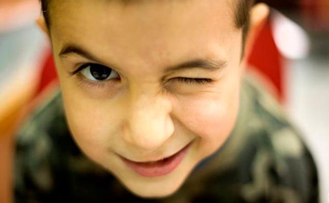 Descripción de foto - niño guiñando el ojo frente la cámara. - Crédito de foto - Ok