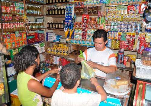 Descripción de foto - tendero atendiendo a niños mientras le compran dulces. - Crédito de foto - Portal Vallenato