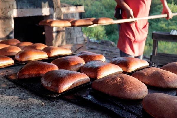 Descripción de foto - Hombre sacando del horno de leña varios panes de mujer recién horneados. - Crédito de foto - El Filósofo