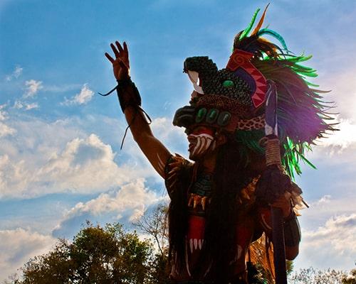 Descripción de foto - Hombre vestio de guerrero maya en el atardecer, levantando su mano. - Crédito de foto - Alberto Ramírez Gordillo