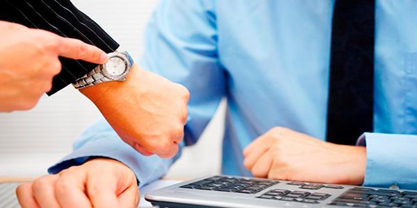 Descripción de foto - Mano de mujer, señalando su reloj de mano, a un hombre que está sentado frente a su escritorio. - Crédito de foto - La 100 Cineradios