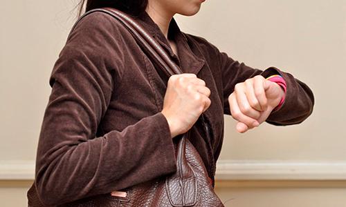 Descripción de foto - Mujer caminando mientras ve el reloj de su muñeca. - Crédito de foto - TN