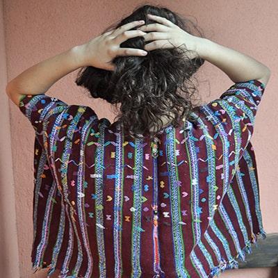 Descripción de foto - Mujer de espaldas portando el huipil de Patzicía. - Crédito de foto - Ixchel Textiles