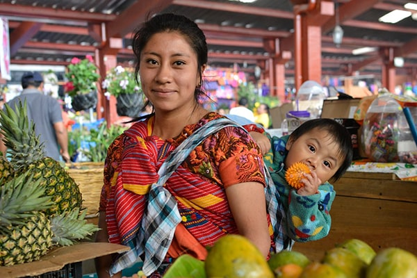 Descripción de foto - Mujer indígena guatemalteca, en el mercado, llevando en su espalda a su hijo. - Crédito de foto - Ministerio de Trabajo