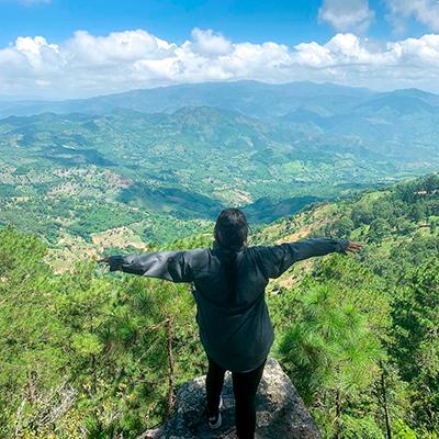 Descripción de foto - Mujer parada sobre una roca, alzando los brazos, con vista a la naturaleza del municipio de Ipala. - Crédito de foto - kareniskarma - instagram