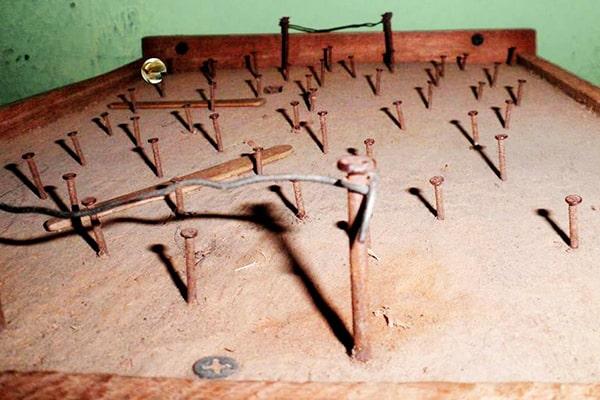 Descripción de foto - futillo con clavos puestos, con una canica en el fondo. - Crédito de foto - Bruno Besamusca