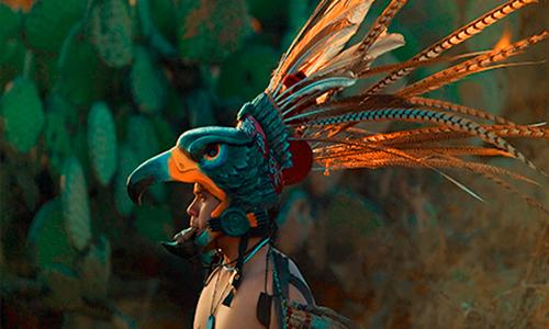Descripción de foto - guerrero maya con corona de ave llena de blumas y pintado de color jade. - Crédito de foto - Sociedad histórica