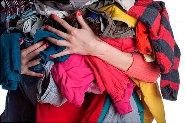 Descripción de foto - mujer sosteniendo muchas prendas de ropa en sus brazos. - Crédito de foto - Significado de los sueños