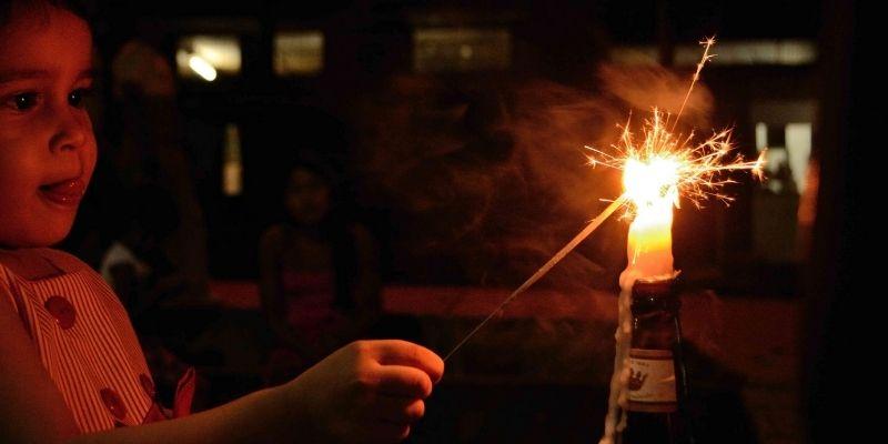 Descripción de foto - niña sosteniendo una estrellita mientras enciende una vela. - Crédito de foto - Periódico la última