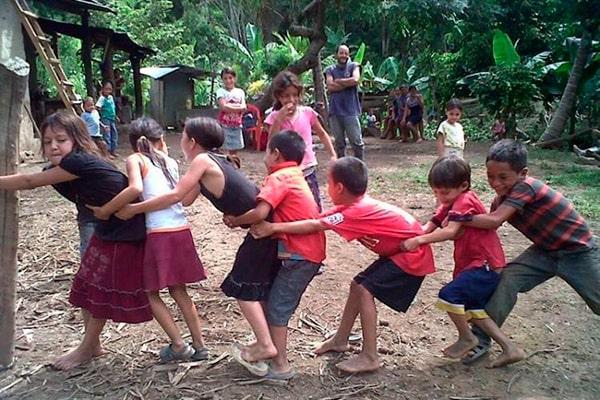 Descripción de foto - niños en una aldea jugando arranca cebollas abrazados a un palo de madera. - Crédito de foto - Noé Lemus
